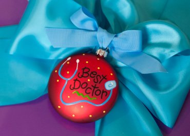Coton Colors Painted Christmas Ornaments. The Glass 90mm Oval Best Doctor Ornament Is Designed with a Stethoscope Accented By Artistic Best Doctor! Writing on the Front and Features a Prescription Pad on the Back