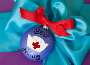 Coton Colors Painted Christmas Ornaments. The Glass 90mm Oval Best Nurse Ornament Is Designed with a Traditional Nurse's Cap and Red Cross Accented By Artistic Best Nurse! Writing on the Front and Features a Band Aid on the Back.