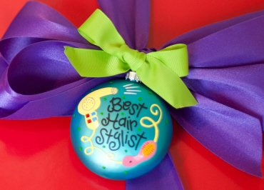 Coton Colors Painted Christmas Ornaments. The Glass 90mm Oval Best Hair Stylist Ornament Is Designed with a Colorful Hair Dryer and Brush Accented By Artistic Best Hair Stylist! Writing on the Front and Features Hairspray on the Back.